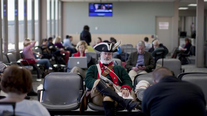 FILE - In this Wednesday, Jan. 4, 2012 file photo, tea party supporter William Temple, of Brunswick, Ga., dressed in a Revolutionary War-era military uniform sits in the Des Moines Airport waiting to fly home after the Iowa caucus in Des Moines, Iowa. (AP Photo/Evan Vucci)