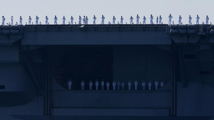 Sailors man the rails of the USS Carl Vinson, a Nimitz-class aircraft carrier, as it departs its home port in San Diego, California