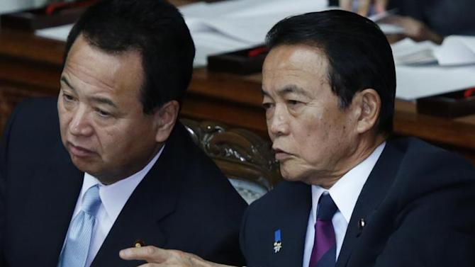 Japan's Finance Minister Aso talks with Economics Minister Amari at the lower house of parliament in Tokyo