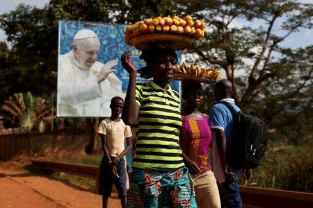 Women carrying fruits and vegetables on their heads walk past a billboard with a photograph of Pope Francis, Bangui, Central African Republic