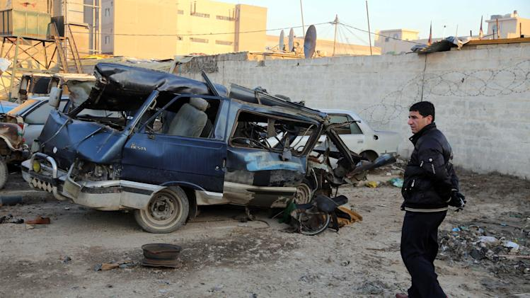 An Iraqi man inspects a minibus damaged in a car bomb attack in Baghdad, Iraq, Monday, Dec. 16, 2013. Iraqi officials say bombings in and around Baghdad have killed and wounded tens of people. (AP Photo/Karim Kadim)