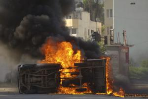 An overturned car burns after it was set on fire by …