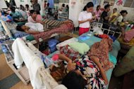 Patients lie on beds in a charity-run Yangon clinic. Figures from the WHO show Myanmar spent just $12 per capita (or 2% of GDP) on health in 2009, of which only one dollar came from the government, with the remainder cobbled together by NGOs and patients