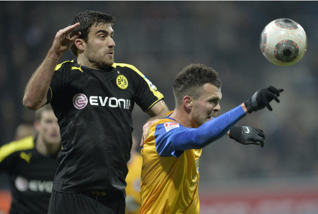 Dortmund's Sokratis of Greece, left, and Braunschweig's Orhan Ademi of Switzerland, right, challenge for the ball during the German Bundesliga soccer match between Eintracht Braunschweig and B