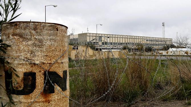 In this Tuesday, Nov. 25, 2014 photo, a rusting barrel with the United Nations logo imprinted on it lies behind barbed wire encircling the terminal building of the long-abandoned Nicosia airport that lies inside a United Nations-controlled buffer zone separating the breakaway Turkish speaking north of ethnically divided Cyprus from the internationally recognized Greek speaking south. Once an emblem of the young republic's growing confidence just 14 years after independence from British colonial rule, the airport overnight became a symbol of a future hijacked by unresolved conflict. (AP Photo/Petros Karadjias)
