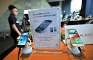<p>A man walks past Samsung smart phones at a mobile phone shop in Seoul on August 27, 2012. Samsung -- the world's top mobile and smartphone maker -- was ordered by a US jury in August to pay Apple $1.05 billion in damages for illegally copying iPhone and iPad features for its flagship Galaxy S smartphones.</p>