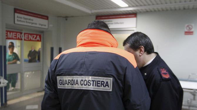 Italian Coast Guard officers stand in front of an emergency entrance of the Antonio Perrino hospital in Brindisi