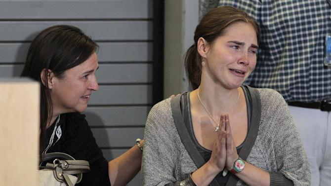 Amanda Knox motions to cheering supporters as her mother, Edda Mellas, looks on at a news conference shortly after her arrival at Seattle-Tacoma International Airport Tuesday, Oct. 4, 2011, in Seattle. It's been four years since the University of Washington student left for the study abroad program in Perugia and landed in prison. The group Friends of Amanda Knox and others have been awaiting her return since an Italian appeals court on Monday overturned her conviction of sexually assaulting and killing her British roommate, Meredith Kercher. (AP Photo/Elaine Thompson)