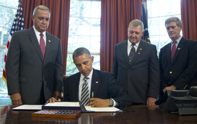 President Barack Obama signs the Honoring America's Veterans and Caring for Camp Lejeune Families Act of 2012, Monday, Aug. 6, 2012, in the Oval Office at the White House in Washington. From left are, Rep. Jeff Miller, R-Fla., Jerry Ensminger, former Master Sergeant, USMC, who served at Camp Lejeune and advocated on behalf of affected veterans and families, and Rep. Brad Miller, D-Fla.. (AP Photo/Haraz N. Ghanbari)
