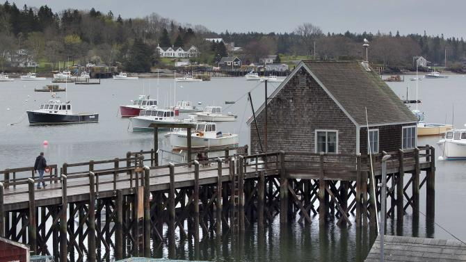 A man walks out on a wharf in Friendship, Maine, Thursday, May 10, 2012. Two lobster boats were recently sunk by vandals in Friendship. The dispute among tightlipped lobstermen points to the unwritten laws of the sea: Fishermen mete out justice themselves, sometimes with violent results.(AP Photo/Robert F. Bukaty)