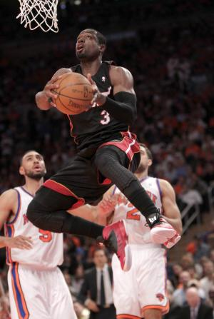 Miami Heat's Dwyane Wade, center, drives to the hoop as New York Knicks' Jared Jeffries, left, and Landry Fields look on in the first half of an NBA basketball game in New York, Sunday, April 15, 2012. (AP Photo/Seth Wenig)