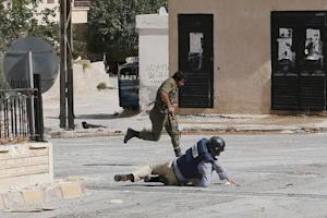 AFP reporter Sammy Ketz hits the ground as a Syrian …