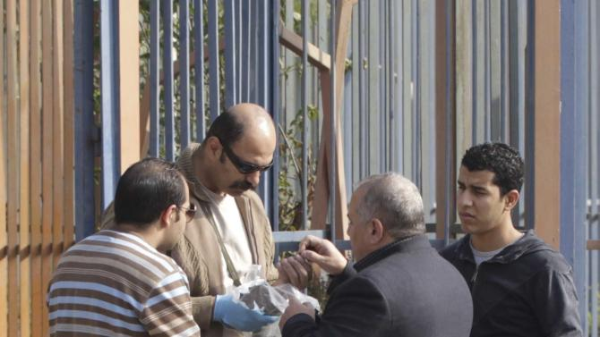 Egyptian security officials inspect the site of a bomb blast near the Alf Maskan district of Cairo