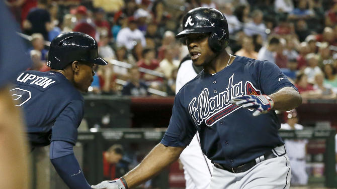Atlanta Braves' Justin Upton, right, celebrates his two-run home run against the Arizona Diamondbacks, his former team, with teammate and brother  B.J. Upton during the sixth inning of a baseball game, on Monday, May 13, 2013, in Phoenix. (AP Photo/Ross D. Franklin)