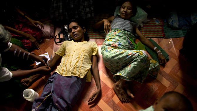 In this Sept. 1, 2012 photo, an HIV-infected woman, center left, gets her medicine through intravenous drips after fainting while another HIV patient is also treated in a hut shared with other HIV-infected patients at an HIV/AIDS center on the outskirts of Yangon, Myanmar. Following a half century of military rule, care for HIV/AIDS patients in Myanmar lags behind other countries. Half of the estimated 240,000 people living with the disease are going without treatment and 18,000 are dying from it every year. (AP Photo/Alexander F. Yuan)