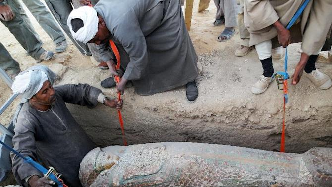 This photo released on Thursday, Feb. 13, 2014 by Egypt's Supreme Council of Antiquities, shows Egyptian men digging up a preserved wooden sarcophagus that dates back to 1600 BC, when the Pharaonic 17th Dynasty reigned, in the ancient city of Luxor, Egypt. Egypt's Antiquities Minister says Spanish archeologists have unearthed a 3,600-year-old mummy in the ancient city of Luxor. (AP Photo/Egypt's Supreme Council Of Antiquities)