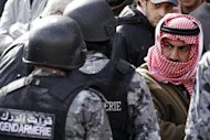 &lt;p&gt;A Jordanian protester looks at riot policemen standing guard amid demonstrators rallying against hikes in fuel prices in Amman.&lt;/p&gt;