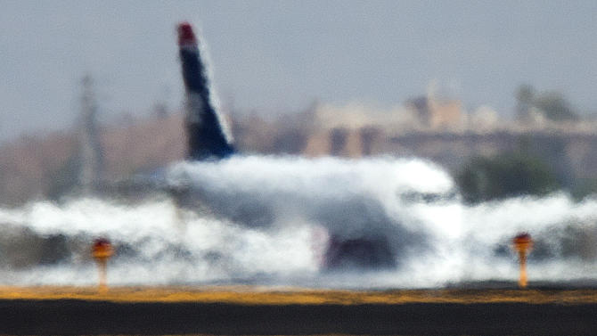 A jet looks like it is melting into the runway as it is distorted by the heat waves rising up from the north runway at Sky Harbor International Airport, Friday, June 28, 2013, the hottest day of the year so far. (AP Photo/The Arizona Republic, Tom Tingle) MARICOPA COUNTY OUT; MAGS OUT; NO SALES