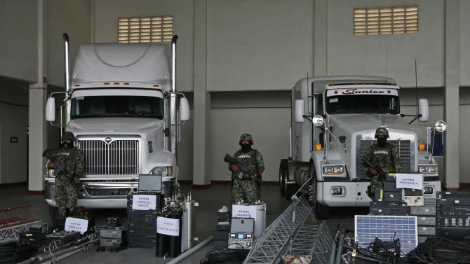FILE - In this Sept. 8, 2011 file photo, members of the Navy stand guard over seized telecommunications equipment, allegedly built by the Zetas drug cartel, during a media presentation in Veracruz, Mexico. The Mexican army and marines have seized hundreds of pieces of communications equipment in at least three operations since September that offer a firsthand look at a surprisingly far-ranging and sophisticated infrastructure. According to authorities, the network was built around 2006 by the Gulf cartel, a narcotics-trafficking gang that employed a group of enforcers known as the Zetas who had defected from Mexican army special forces. (AP Photo/Marco Ugarte, File)