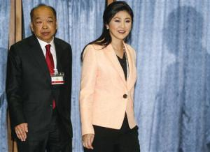Thailand's PM Yingluck and Deputy PM Surapong arrive before a meeting with the Election Commission at the Royal Thai Air Force Academy in Bangkok
