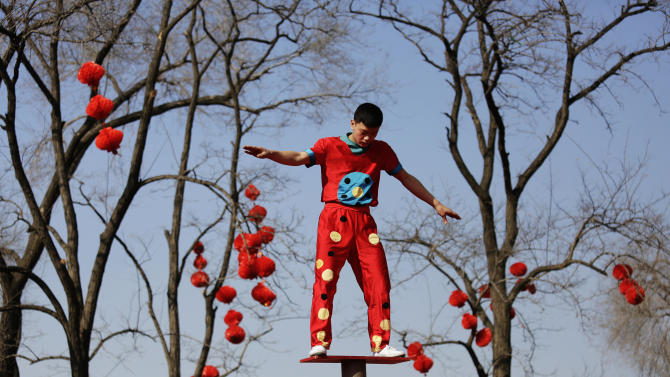 A performer balances on metalic cylinders at the Longtan park as the Chinese Lunar New Year is celebrated in Beijing