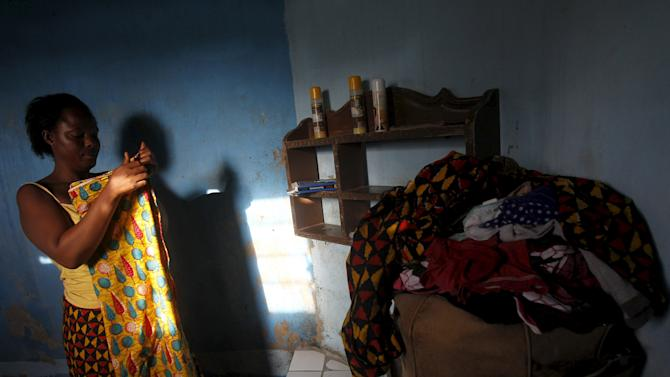 Nicole Gbalou, 31, arranges her clothes at her home in the Cocody Danga slum in Abidjan