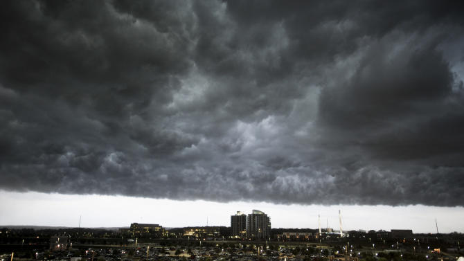 Heavy storm clouds darken the sky as rain and wind gusts blow over downtown Omaha, Neb., Monday, June 20, 2011. (AP Photo/Dave Weaver)