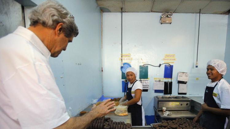 U.S. Secretary of State Kerry visits a donut shop during a tour of the damage from super typhoon Haiyan in Tacloban