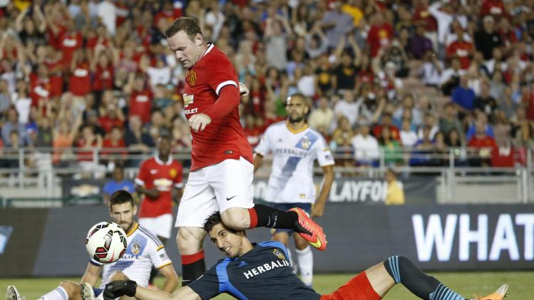 Manchester United forward Rooney scores past Los Angeles Galaxy's goalkeeper Penedo during the first half of their international soccer friendly match in Pasadena