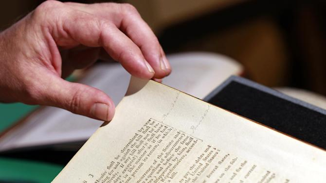 George Washington's notes in the margin are seen as Chris Coover, senior specialist for rare books & manuscripts at Christie's, shows President George Washington's personal copy of the Acts of the first Congress (1789), containing the U.S. Constitution and the proposed Bill of Rights, during a media availability, Tuesday, June 12, 2012, in Washington. The book will go on auction June 22nd and is expected to bring between $2-3 million. (AP Photo/Alex Brandon)