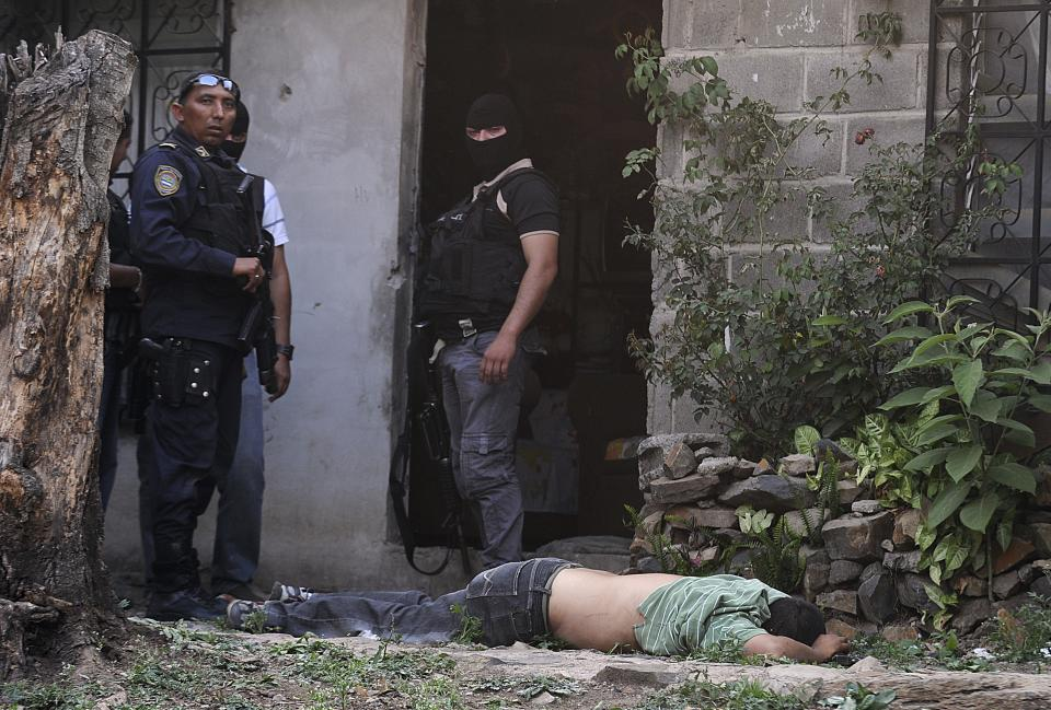 In this April 7, 2013 photo, police stand next to the body of a man who was killed during a shootout with police who were carrying out an offensive against gang members in Tegucigalpa, Honduras. The officers had surrounded a house where two gangsters had holed up after a chase with police. (AP Photo/Fernando Antonio)