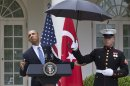 President Barack Obama leans out from under an umbrella to check if it's still raining, during a joint news conference with Turkish Prime Minister Recep Tayyip Erdogan, Thursday, May 16, 2013, in the Rose Garden of the White House in Washington. (AP Photo/Jacquelyn Martin)