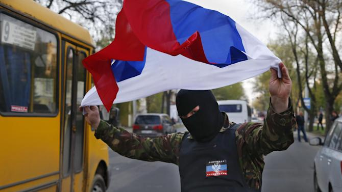 """A masked pro Russia protestor waves the Russian flag in Donetsk, eastern Ukraine, Tuesday, April 22, 2014. U.S. Vice President Joe Biden warned Russia on Tuesday that """"it's time to stop talking and start acting"""" to reduce tension in Ukraine, offering a show of support for the besieged nation as an international agreement aimed at stemming its ongoing crisis appeared in doubt. (AP Photo/Sergei Grits)"""
