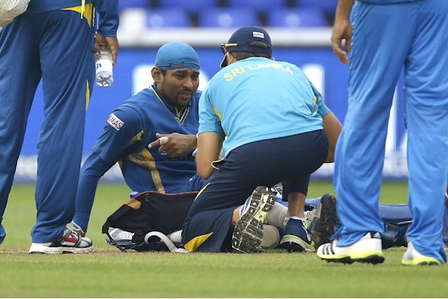 Sri Lanka's Tilakaratne Dilshan is treated for an injury during the ICC Champions Trophy semifinal between India and Sri Lanka at the Cardiff Wales Stadium,  in Cardiff, Thursday, June 20, 2013