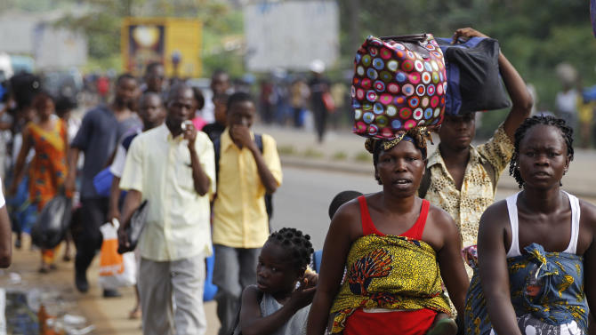 Residents of the Abobo district carry their belongings as they flee the neighborhood which has become a hub for street violence in the nation's ongoing political standoff, in Abidjan, Ivory Coast, Monday, Feb. 28, 2011. In a dramatic escalation of the nation's conflict, Belarus has violated an international arms embargo by sending three attack helicopters to military forces supporting Ivory Coast's longtime ruler who refuses to cede power, alleged a Sunday statement issued by the office of United Nations Secretary-General Ban Ki-moon. (AP Photo/Rebecca Blackwell)