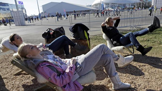 Women lay in the sun outside the Swiss House at the 2014 Winter Olympics, Wednesday, Feb. 12, 2014, in Sochi, Russia. Temperatures are predicted near 60 degrees Fahrenheit in Sochi on Wednesday