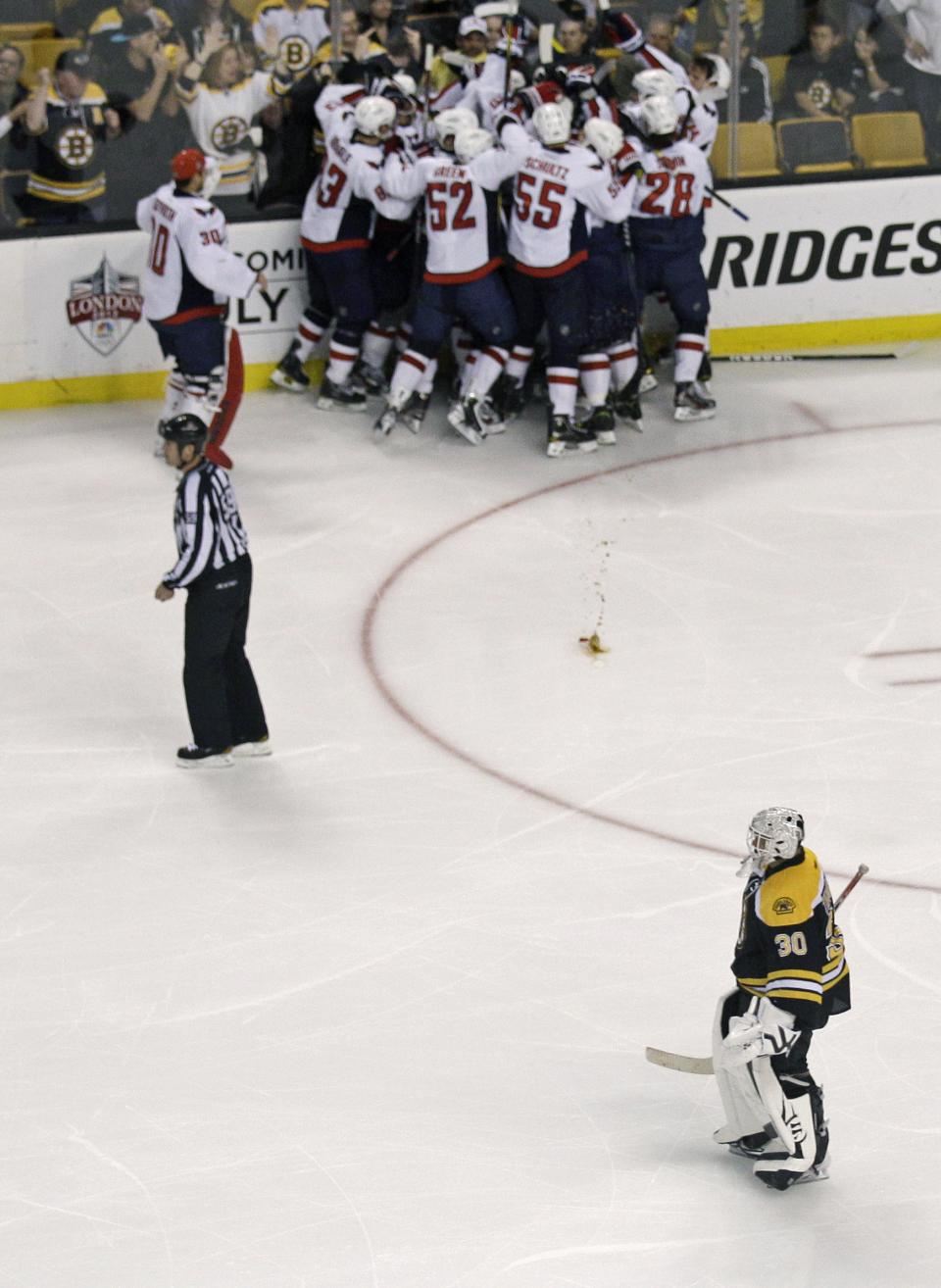 As the Washington Capitals celebrate their win, Boston Bruins goalie Tim Thomas (30) skates off the ice following Game 7 of an NHL hockey Stanley Cup first-round playoff series, in Boston on Wednesday, April 25, 2012. The Capitals won 2-1 in overtime. (AP Photo/Charles Krupa)
