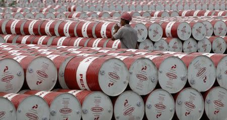 File photo of a worker walking in between oil barrels at Pertamina's storage depot in Jakarta