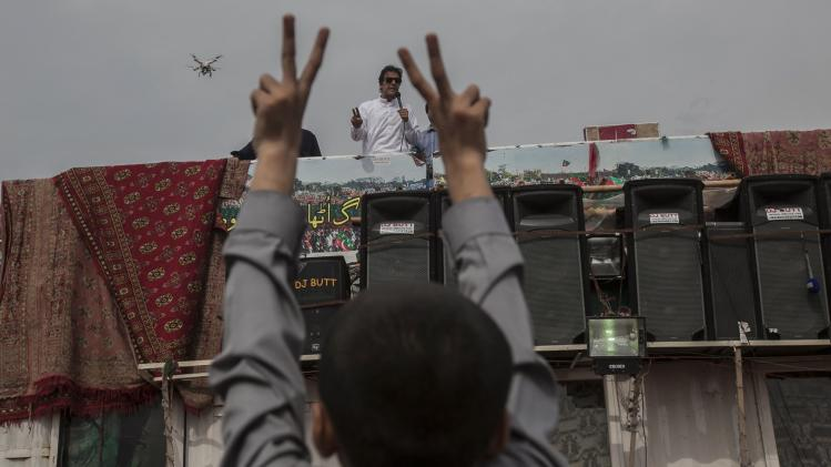 Imran Khan addresses supporters while a boy gestures in Islamabad