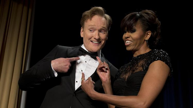 First lady Michelle Obama and late-night television host and comedian Conan O'Brien gesture to his tie at the White House Correspondents' Association Dinner at the Washington Hilton Hotel, Saturday, April 27, 2013, in Washington.  (AP Photo/Carolyn Kaster)