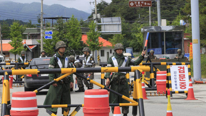 South Korean army soldiers stand guard on the road to search for a South Korean conscript soldier who is on the run after a shooting incident at a temporary checkpoint in Goseong, South Korea, Sunday, June 22, 2014. The military searched Sunday for an armed South Korean soldier who fled after killing five of his comrades and wounding seven at an outpost near the North Korean border.(AP Photo/Ahn Young-joon)