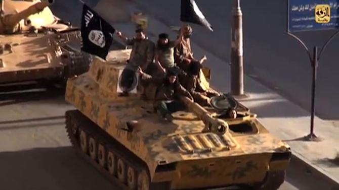 A screen grab taken from a video released on July 1, 2014, by Welayat Raqa allegedly shows members of the Islamic State group parading on top of a tank in the northern Syrian city of Raqa