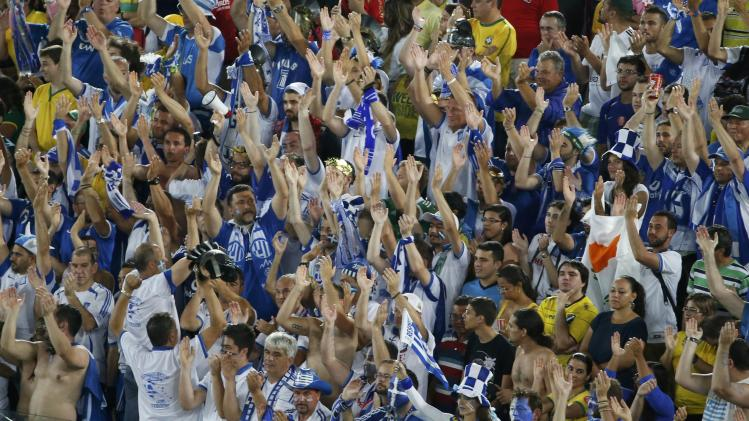 Fans of Greece cheer their team on during their 2014 World Cup Group C soccer match against Japan at the Dunas arena in Natal