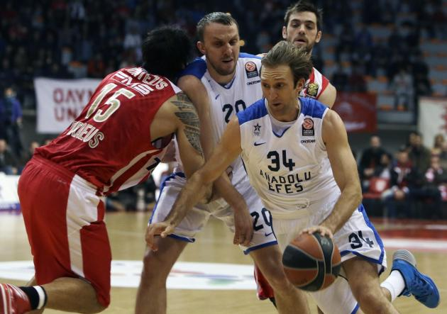 Olympiakos' Georgios Printezis, left, tries to stop Anadolou Efes' Dusko Savanovic, center, as his teammate Dusko Savanovic drives the ball during their Euroleague basketball match of Top 16 i