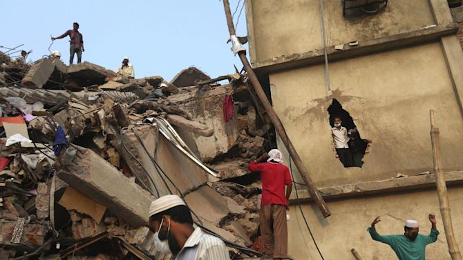 Bangladeshi rescue workers search the rubble at the site of a building that collapsed Wednesday in Savar, near Dhaka, Bangladesh, Friday, April 26, 2013. The death toll reached hundreds of people as rescuers continued to search for injured and missing, after a huge section of an eight-story building that housed several garment factories splintered into a pile of concrete.(AP Photo/Kevin Frayer)
