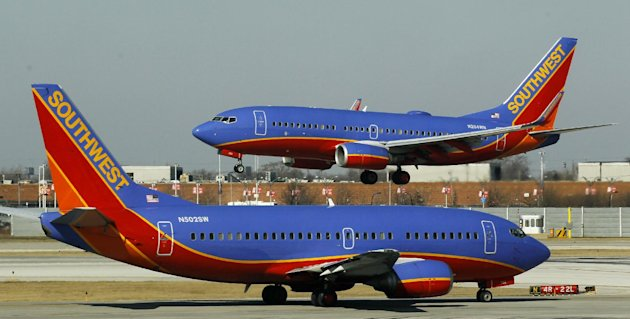 FILE - In this Feb. 9, 2012, file photo, a Southwest Airlines Boeing 737 waits to take off at Chicago&#39;s Midway Airport as another lands. The government can require airlines to show consumers a total ticket price that includes taxes and fees in print and online ads, the U.S. Court of Appeals said Tuesday, July 24, 2012, rejecting an industry challenge to a series of consumer protection regulations. The Department of Transportation, which issued the regulations last year, has the authority to regulate unfair and deceptive airline industry practices, the three-member panel said in its ruling. The ruling also covers two other regulations: A requirement that airlines allow consumers who purchase tickets more than a week in advance the option of canceling their reservations without penalty within 24 hours after purchase, and a ban on airlines increasing the price of tickets or baggage fees after tickets have been bought. The rules had been challenged by Spirit and Southwest airlines, with the support of two major airline industry trade associations. (AP Photo/Charles Rex Arbogast, File)