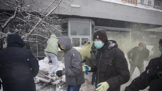 In this photo taken on Friday, March 15, 2013, members of a pro-Kremlin youth group attack pushers of spice, a synthetic drug, one of which is swinging a bat at them in Moscow, Russia. Russian officials and anti-drugs campaigners say that spice has become one of the most dangerous drugs widely available to youngsters and almost impossible to ban because of the constantly changing chemical ingredients. (AP Photo/Alexander Zemlianichenko Jr)