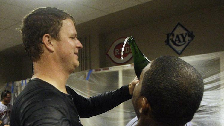 San Francisco Giants pitcher Matt Cain, left, celebrates with Santiago Casilla in the locker room after they defeated the Cincinnati Reds 6-4 in Game 5 of the National League division baseball series, Thursday, Oct. 11, 2012, in Cincinnati.  The Giants won the final three games, all in Cincinnati, and advanced to the NL championship series. (AP Photo/David Kohl)
