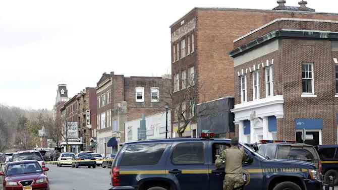 Law enforcement officers block off Main Street  in Herkimer, N.Y., while searching for a suspect in two shootings that killed four and injured at least  two on, Wednesday, March 13, 2013. Authorities were looking for 64-year-old Kurt Meyers, said Herkimer Police Chief Joseph Malone. Officials say guns and ammunition were found inside his Mohawk apartment after emergency crews were sent to a fire there Wednesday morning.  (AP Photo/Mike Groll)