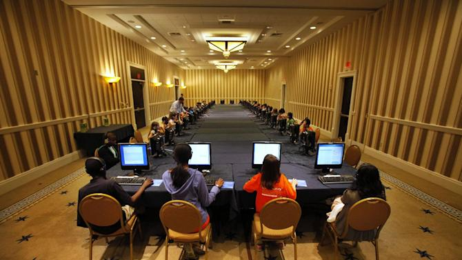 FILE - In this May 29, 2012 file photo, contestants in the National Spelling Bee take the written exam on computers in Oxon Hill, Md., before the oral competition began. Ever wonder if those spelling bee kids know the meanings of some of those big words? Now they'll have to prove that they do. Organizers of the Scripps National Spelling Bee on Tuesday announced a major change to the format, adding multiple-choice vocabulary tests to the annual competition that crowns the English language's spelling champ. (AP Photo/Jacquelyn Martin, File)